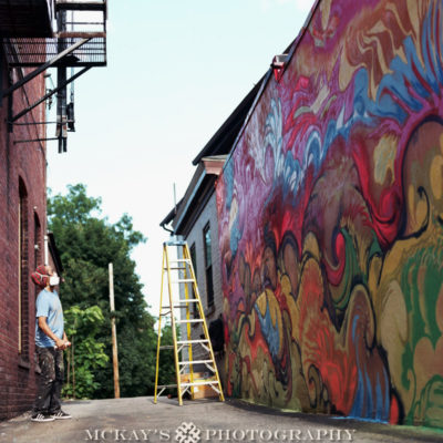 Artist Mike Ming in Rochester painting a Wall Therapy mural on the side of Personal FX Hair Studio in the South Wedge. Film photograph by Heather McKay
