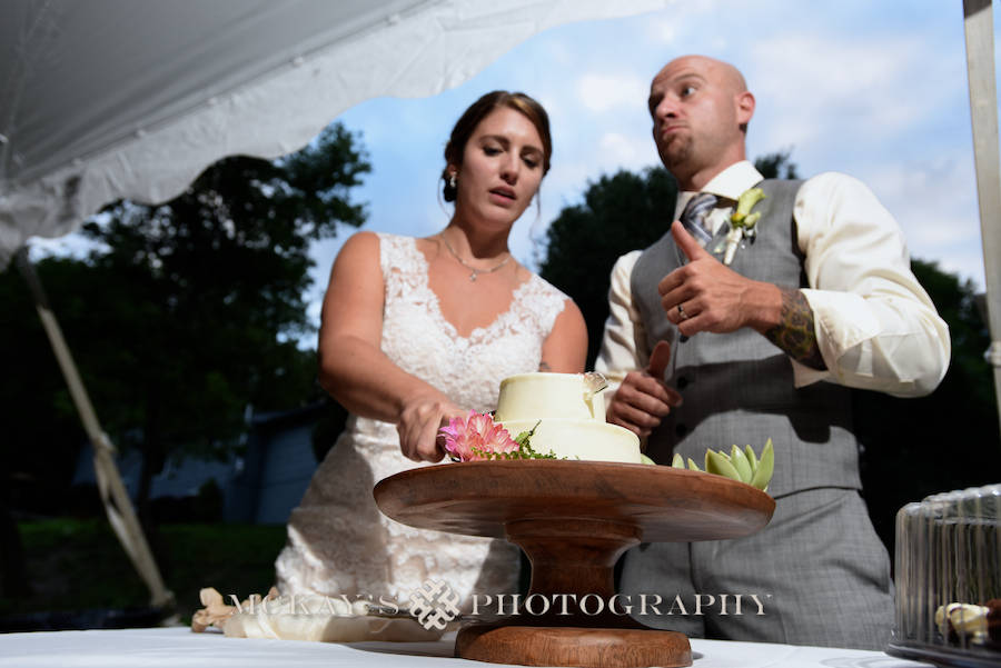 Bride and groom cut their wedding cake at their backyard wedding in the Finger Lakes